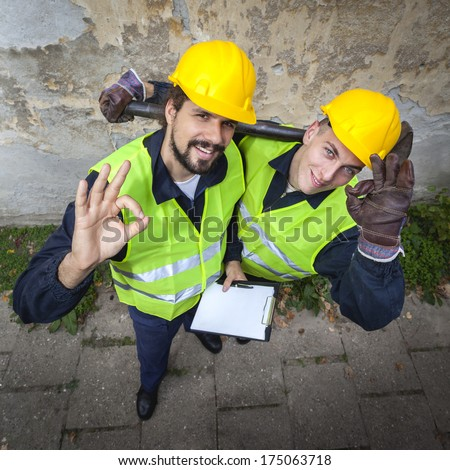 Two manual workers happy with their working conditions smiling, showing O.K. sign, in protective suites, one holding paper and pen, the other one holding big hammer. View from above. Good Work. - stock photo