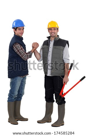 Two manual workers shaking hands - stock photo