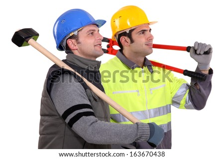 Two manual workers stood together looking into the distance - stock photo