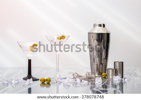 Two Martini cocktails poured over crushed ice in Art Deco glasses with shaker in the background
