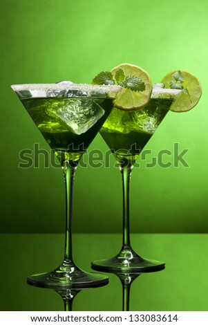 Two martini glasses with green cocktails in green light