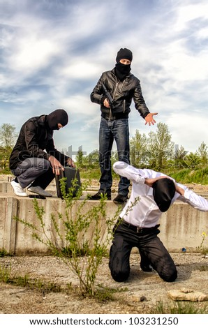Two masked gunman trying to kill businessman. Asks a PIN - stock photo