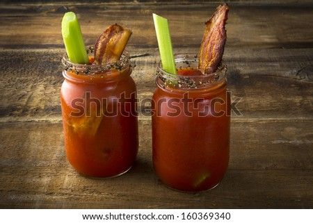 Two mason jar Bloody Marys or Caesars  with  bacon on wood background - stock photo