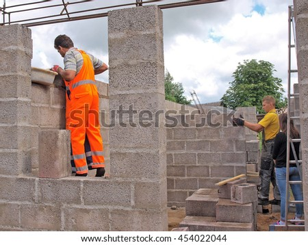 Two masons are building house walls from concrete blocks.