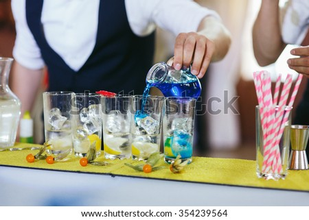 Two master mixologists creating drinks and cocktails at wedding reception - stock photo