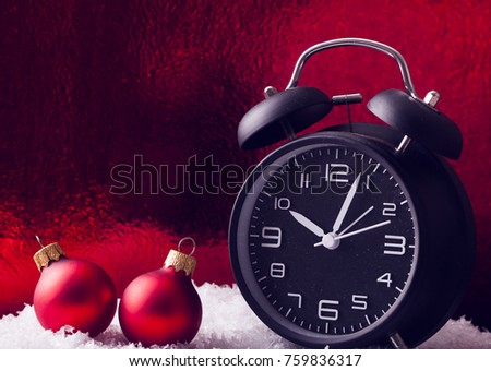 two mate red christmas balls and old vintage alarm clock on white carpet and blur background