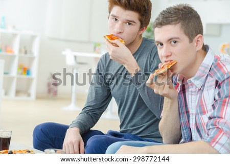 Two mates sharing a pizza - stock photo