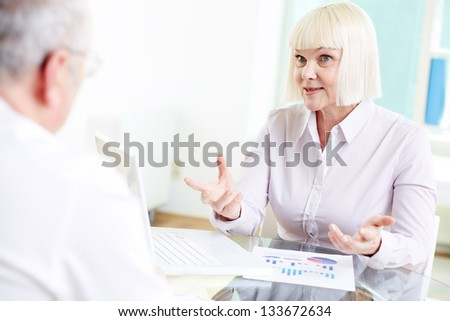 Two mature business partners discussing ideas at meeting - stock photo