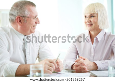 Two mature business partners discussing ideas or plans at meeting