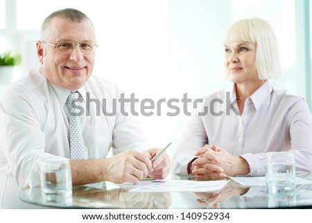 Two mature business partners sitting at workplace - stock photo
