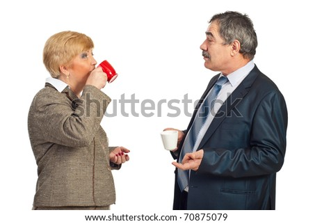 Two mature business people drinking coffee in a business break and having conversation together isolated on white background