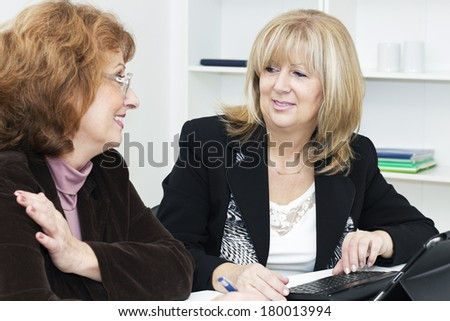 Two mature businesswoman working in the office. - stock photo
