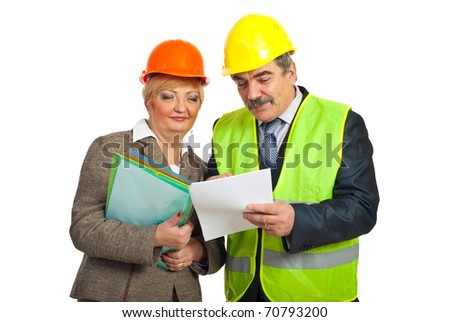 Two mature constructors workers reading contract and wearing security helmets isolated on white background - stock photo