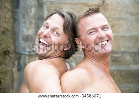 Two mature gay men are laughing and fooling around together.