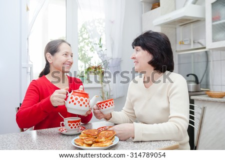 Two mature girlfriends talking over coffee in  kitchen. - stock photo