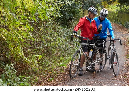 Two Mature Male Cyclists On Ride Looking At Mobile Phone App - stock photo