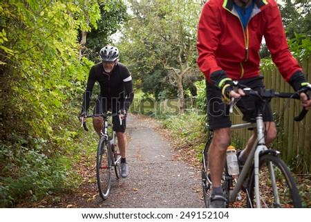 Two Mature Male Cyclists Riding Bikes Along Path - stock photo