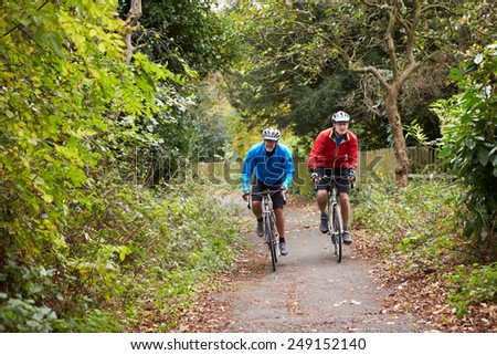 Two Mature Male Cyclists Riding Bikes Along Path - stock photo