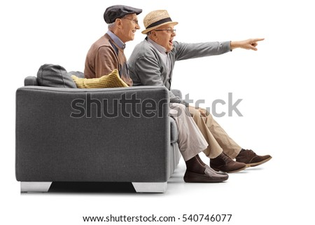 Two mature men sitting on a couch with one of them pointing isolated on white background