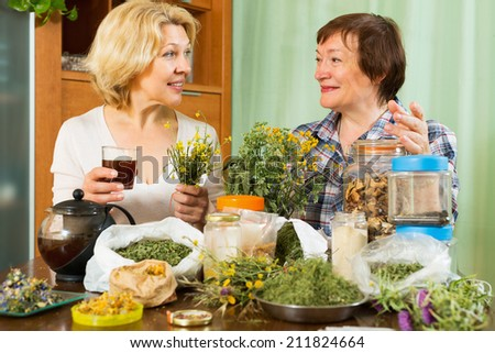 Two mature pensioner sitting at the table with herbal tea and herbs