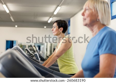 Two mature women are running on a treadmill in the fitness studio