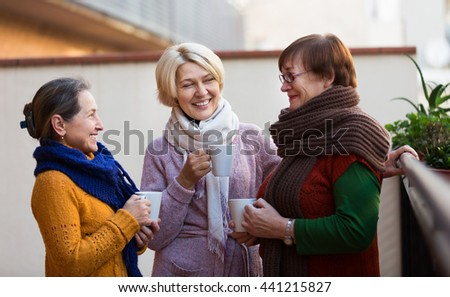Two mature women drinking tea on a balcony and smiling