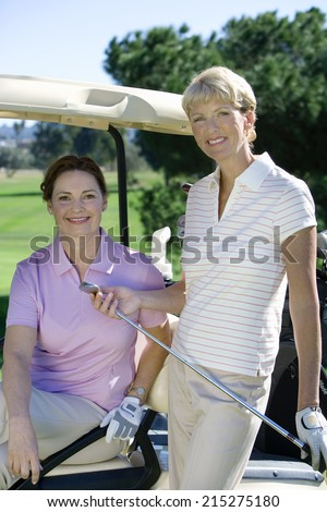 Two mature women posing on golf course, brunette sitting in golf buggy, blonde standing beside her, smiling, portrait