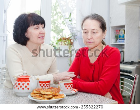 Two mature women talking at kitchen table with a cup of tea. - stock photo