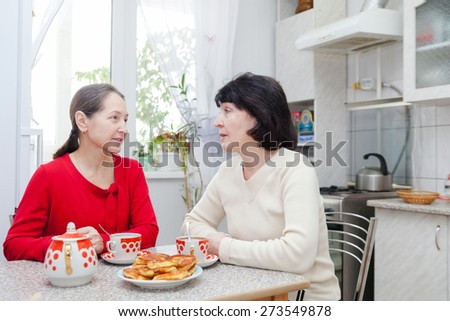 Two mature women talking at   kitchen table with   cup of tea.
