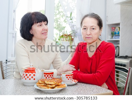 Two mature women talking over coffee in   kitchen.