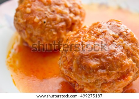 two meatballs in tomato sauce on a white plate
