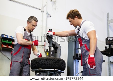 Two mechanics changing tire on a wheel in a car workshop - stock photo