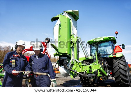two mechanics, farmers with tractors and mowers in background, latest models of farming machinery - stock photo
