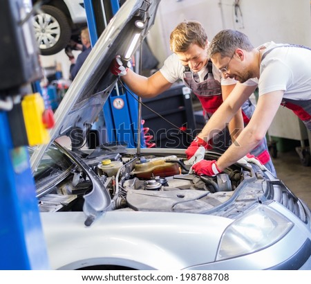 Two mechanics fixing car in a workshop - stock photo