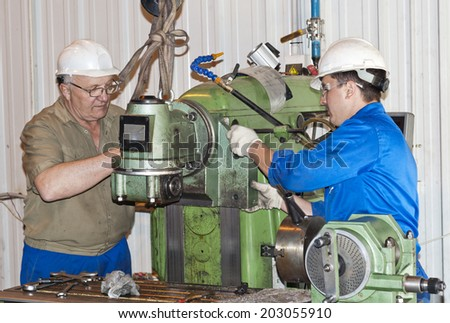 Two mechanics operates the production equipment - stock photo
