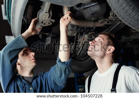 Two mechanics repairing car in garage under the car. - stock photo