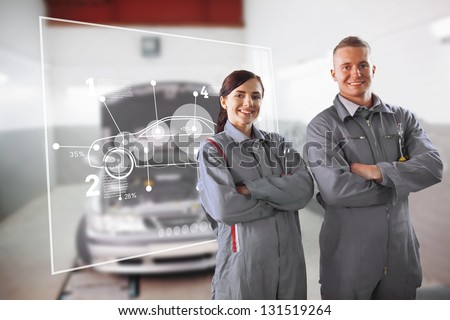 Two mechanics standing in front of a futuristic interface in a garage - stock photo
