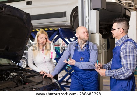Two mechanics trying to cheat sad european female client at workshop