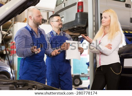 Two mechanics trying to cheat unhappy russian female client at workshop - stock photo