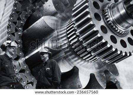 two mechanics, workers with large gears and cogs machinery - stock photo
