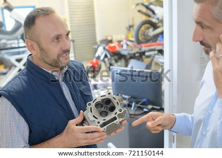 two mechanics working in a garage