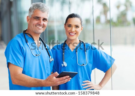 two medical doctors using tablet pc in hospital - stock photo