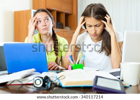 Two melancholy female students working on laptop computers. Focus on the right woman - stock photo