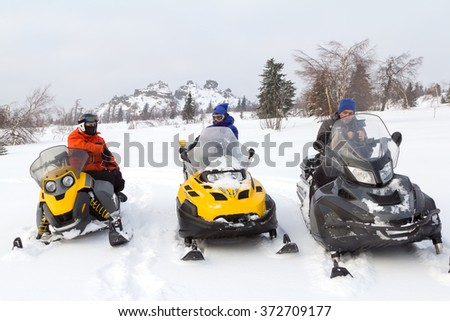 Two men and a woman stopped at a clearing while traveling in the winter woods on snowmobiles.