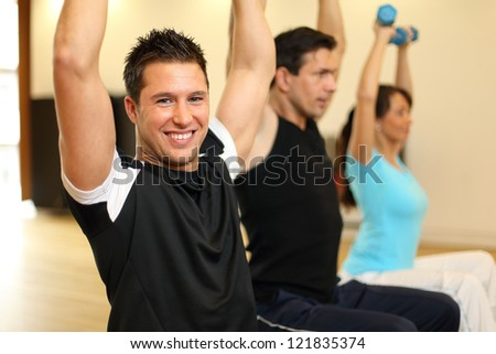 Two men and one woman exercising with dumbbells on gymnastics balls
