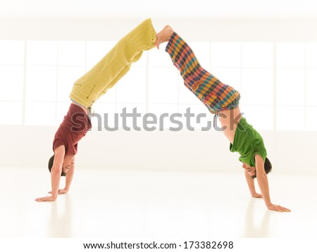 two men are doing yoga partners in a gym - stock photo