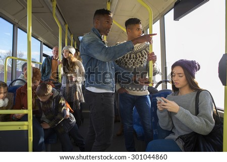 Two men are standing on a bus. There are people around them talking and using technology. - stock photo