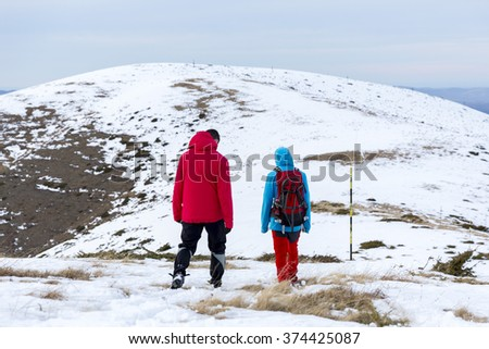 Two men are walking high in the snow in the mountain during the winter.