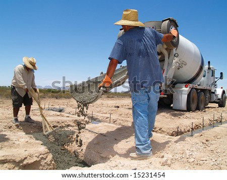 Two men are working on an excavation site.  They are guiding the cement into a trench.  They are looking down at their work.  Horizontally framed shot.