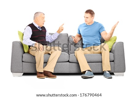 Two men arguing seated on a sofa isolated on white background - stock photo